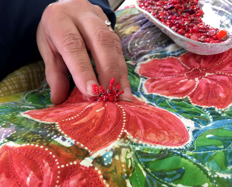 The beaded pistil stitch adds wonderful dimension to the center of the flower in this Hari Agung panel