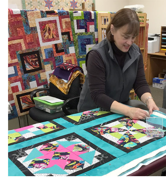 Student from Artistic Artifacts' beginning quilting class taught by Dudley Shugart preparing her top for quilting