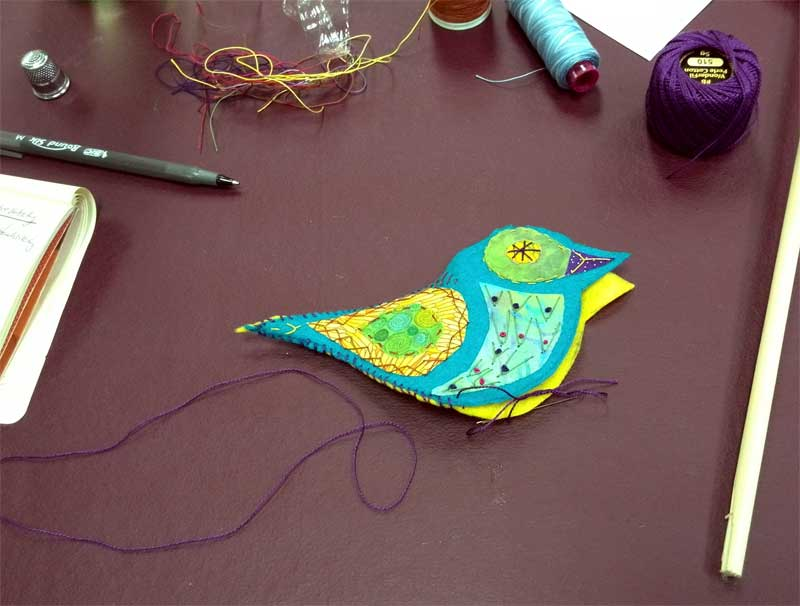 Felt and fabric bird front embellished with hand stitching being whipstitched together with its back