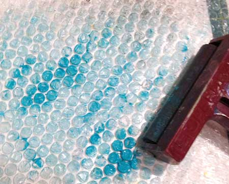 Applying turquoise paint to bubble wrap
