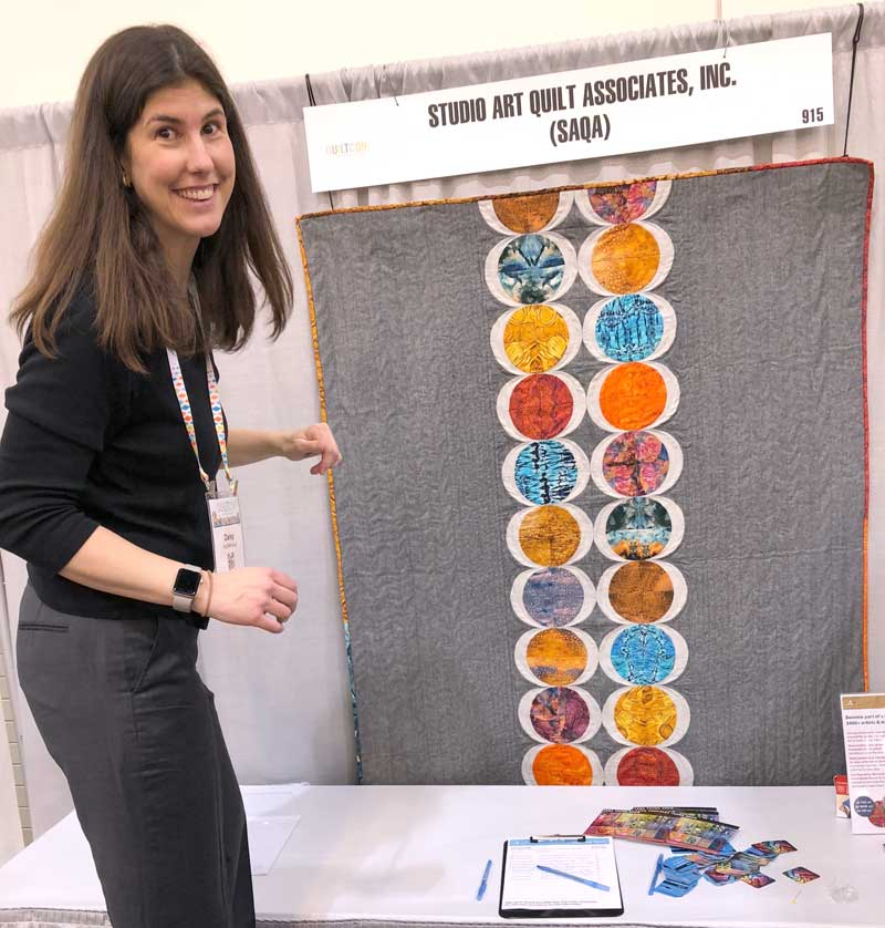 Daisy Aschehoug poses with her quilt in the SAQA booth