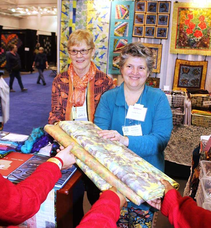 Christine Vinh and Artistic Artifacts owner Judy Gula present Roy Mitchell's quilting students with three bolts of Indonesian-made material for their classroom.