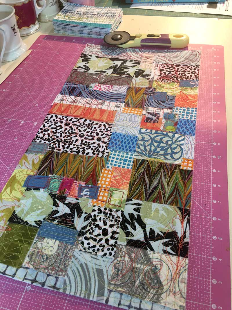 Fabric collaged sheet ready to be cut into postcards