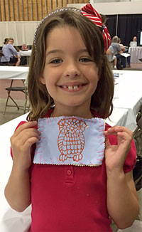 A young show visitor displays her finished quiltlet