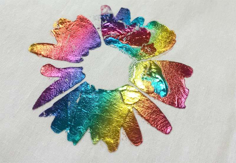 A foiled flower on a cotton fabric swatch