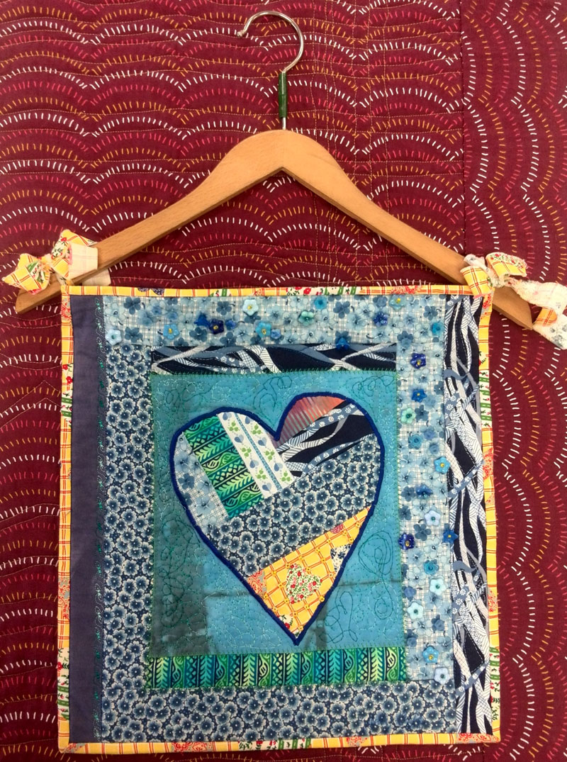 Hanging heart art quilt incorporating vintage clothes hanger by Judy Gula of Artistic Artifacts