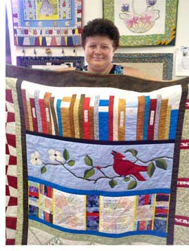 Jana Franklin holding her prize-winning quilt