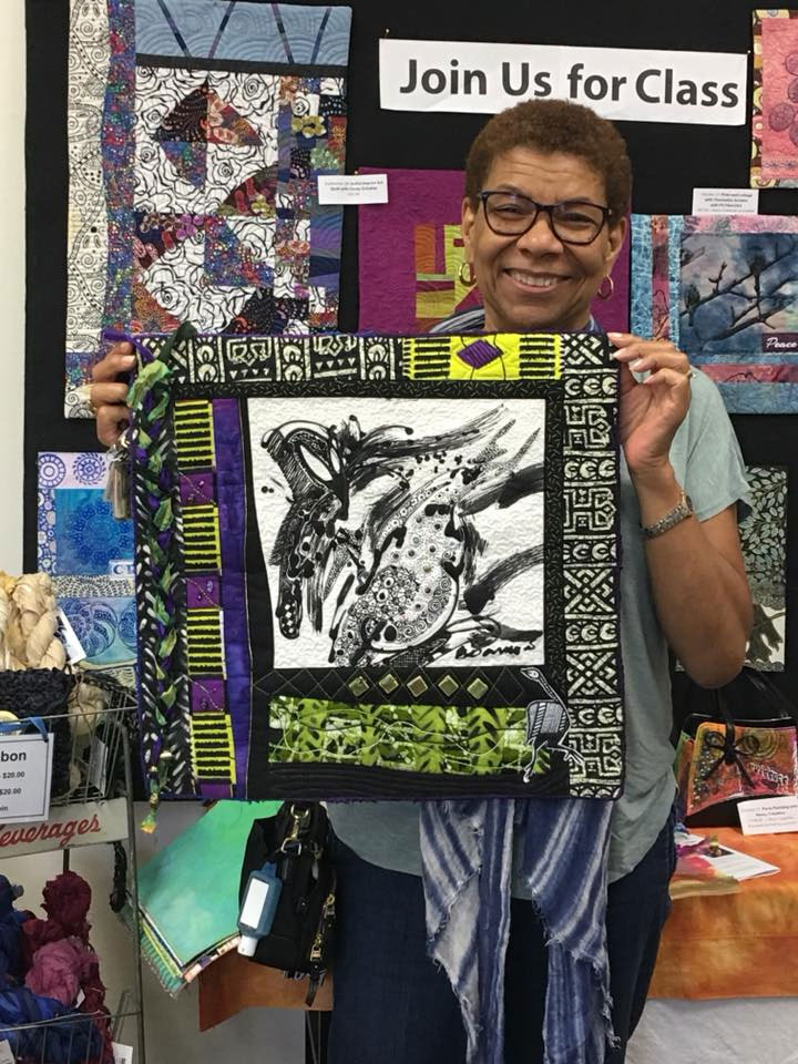 Janet Green holds the batik panel quilt she completed after taking a Judy Gula class at Artistic Artifacts