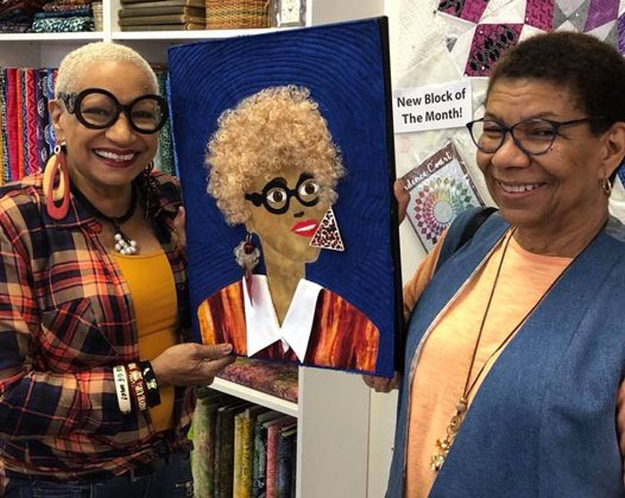 Janet Green poses with her sister and the fiber portrait she created of her