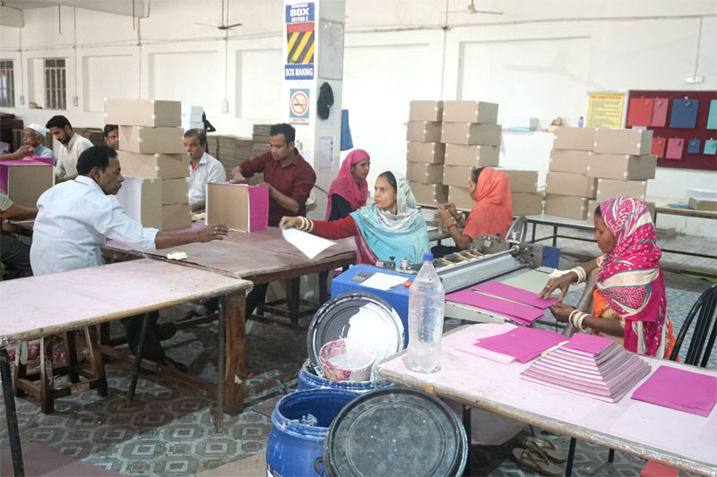 Factory workers at  Salim's Paper covering paper boxes with decorative sheets of handmade paper