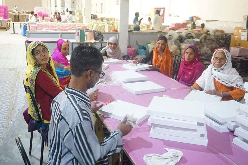 Factory workers at  Salim's Paper creating paper boxes