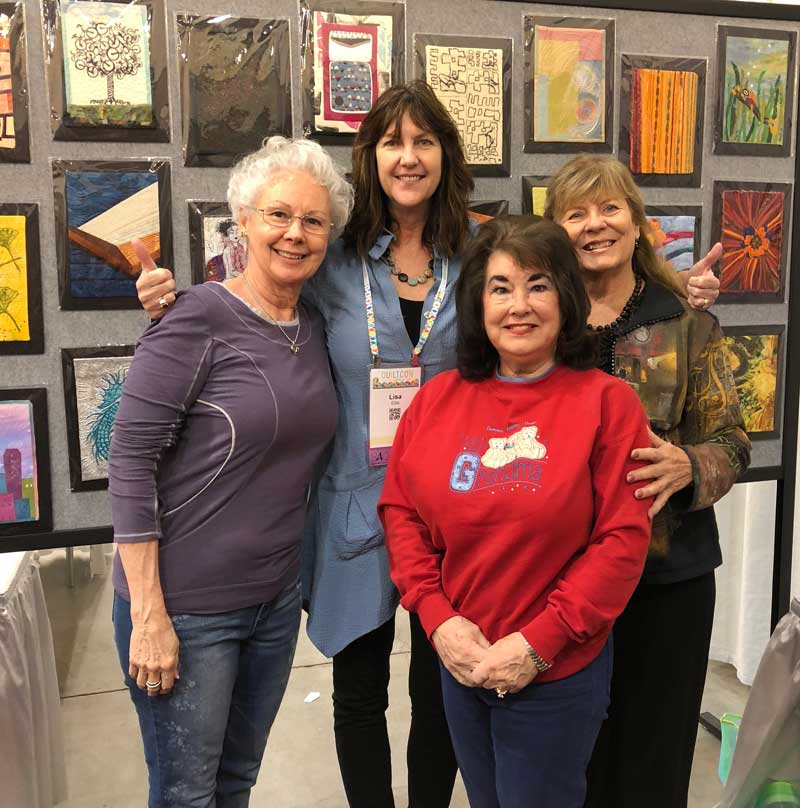 Lisa Ellis poses with QuiltCon attendees in front of the SAQA Trunk Show exhibit