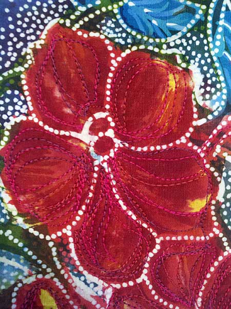 Free motion quilting on red flower panel