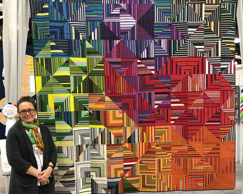 SAQA member Sarah Bond won the eQuilter Quilting Excellence award at Quilt Con