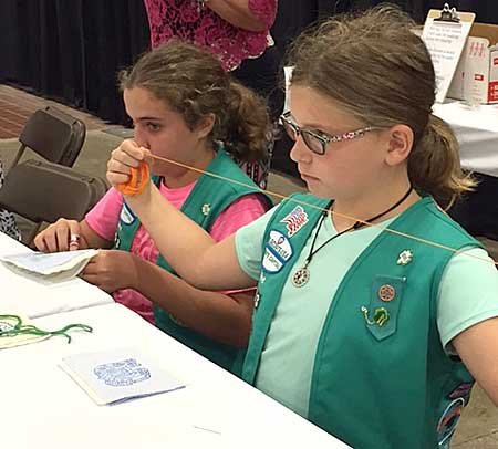 Girl Scout volunteers teaching hand stitching