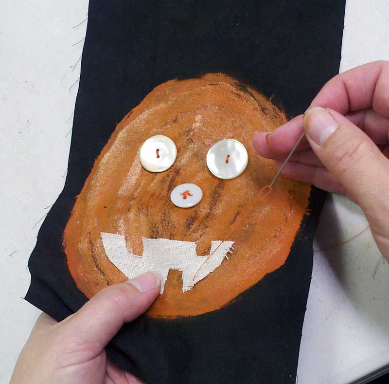 Sewing on the pumpkin's facial features