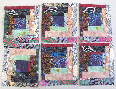 Six scrappy log cabin blocks pieced from Aborigine designed fabric