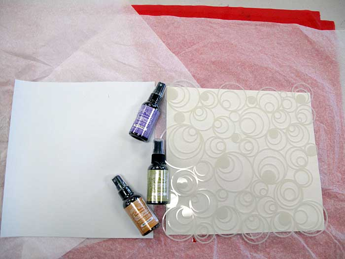 Spray inks and stencils atop Multi-Purpose Cloth inside cover
