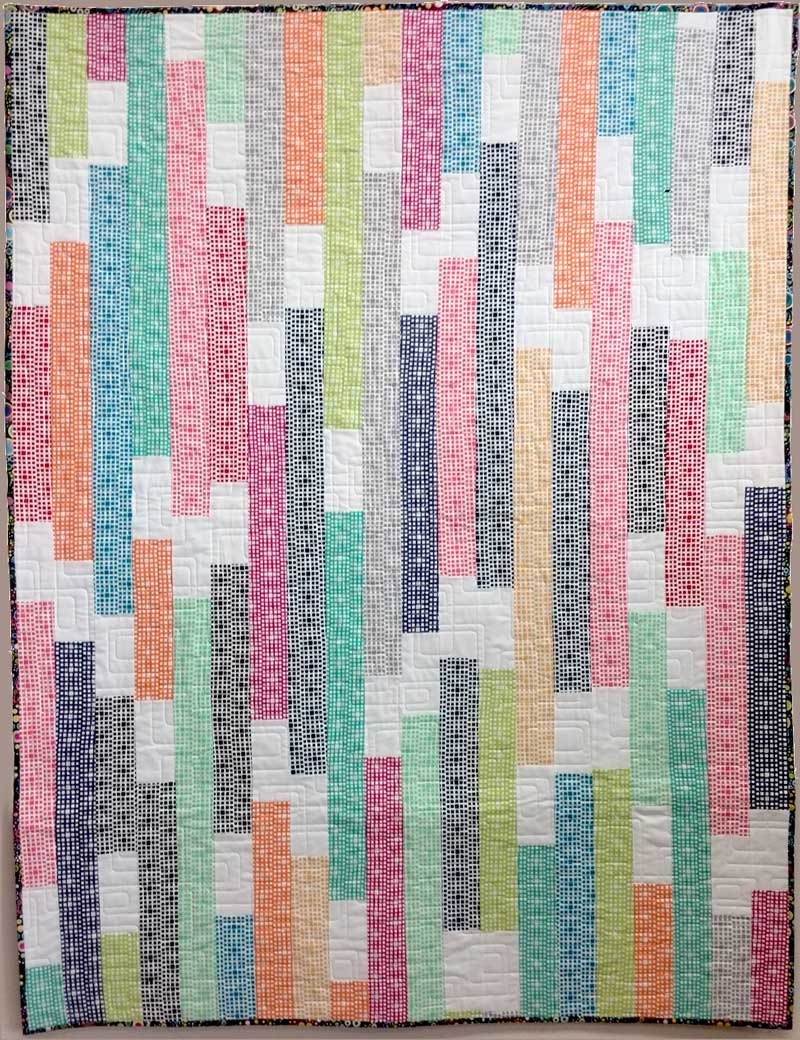 Featuring Squared Elements fabrics by Art Gallery, this modern quilt was strip pieced by Christine Vinh of StitchesnQuilts