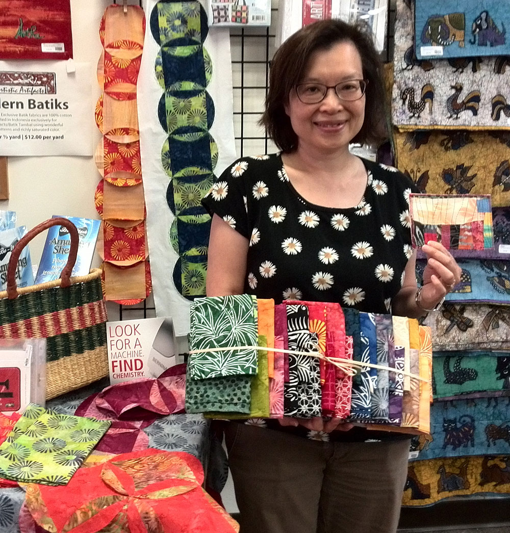 Sue Lee with her Batik Tambal Exclusive Batik fabric prize for being the first to turn in a completed Row by Row Experience quilt.