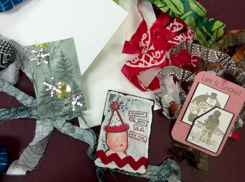 Materials to craft greeting cards using woven fabric strips and Artist Trading Cards
